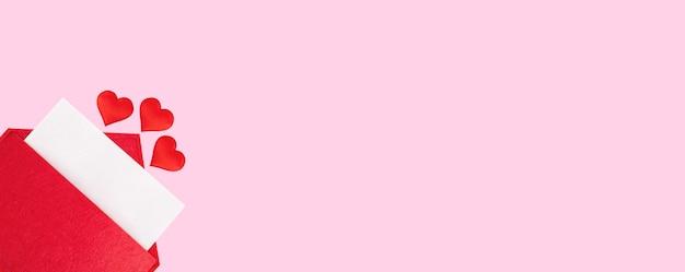 Красный открытый конверт с листом бумаги с сердечками на розовом фоне. день святого валентина