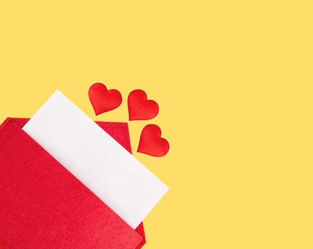노란색 바탕에 하트와 종이의 시트와 함께 빨간 오픈 봉투. 발렌타인 데이 휴일 개념