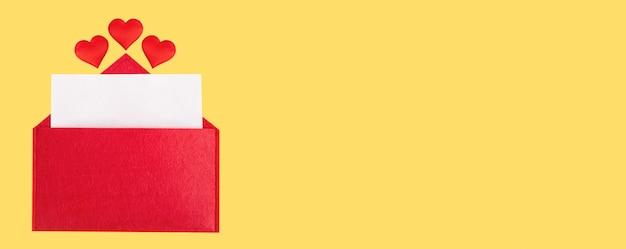 Красный открытый конверт с листом бумаги с сердечками на желтом фоне. день святого валентина