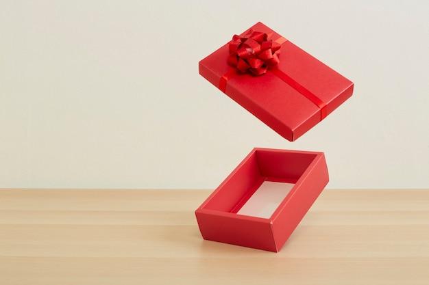 木製のテーブルの背景に赤いリボンと赤いオープンギフトボックス