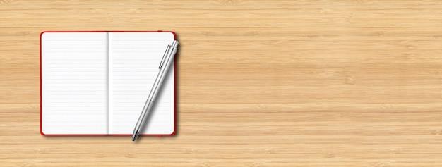 Красный блокнот с открытой подкладкой с ручкой, изолированной на деревянном столе.