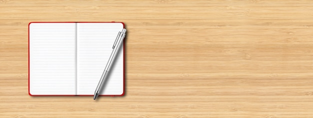 Red open lined notebook  with a pen isolated on wooden table.
