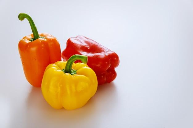 Красный, оранжевый и желтый болгарский перец, изолированные на белом фоне. скопируйте пространство.