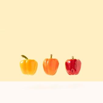 明るいパステルカラーの背景に浮かぶ赤オレンジと黄色のベリーペッパー最小限の食品の概念