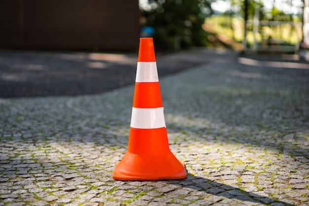 敷石の道に白い縞模様のある赤オレンジ色のコーン。安全と構造のコンセプトを推進します。
