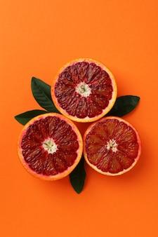 Красные оранжевые половинки и листья на оранжевом изолированном фоне