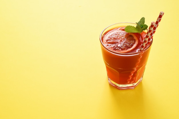 黄色の背景に分離されたガラスの赤オレンジジュース