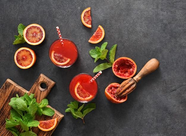 黒いコンクリートの表面にミントが入った赤オレンジジュース夏の飲み物