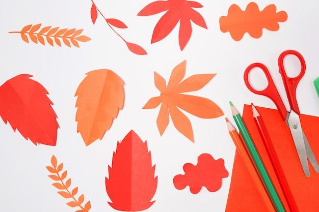 빨간색, 주황색 종이가 흰색 바탕에 나뭇잎. 손으로 만든 종이 접기.