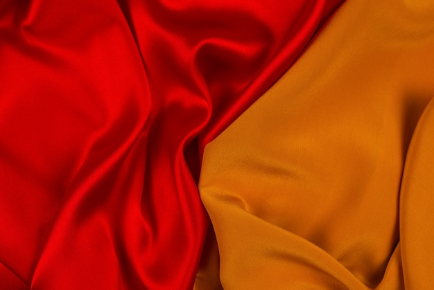 Red and orange silk or satin luxury fabric texture can use as abstract background.