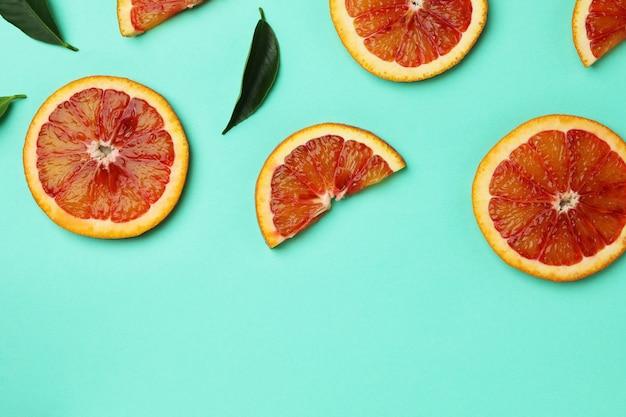 Ломтики красного апельсина и листья на изолированном фоне мяты