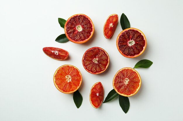Дольки красного апельсина с листьями на белом изолированном фоне