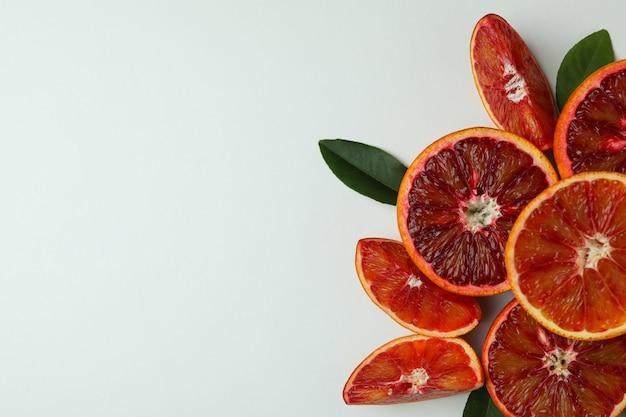 Дольки красного апельсина с листьями на белом Premium Фотографии