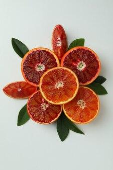 Дольки красного апельсина с листьями на белом