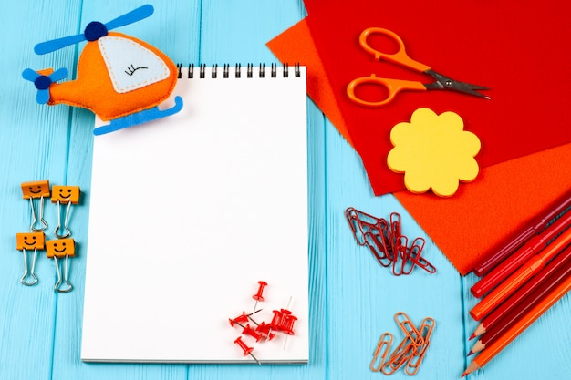 Red and orange stationery and felt helicopter on blue wooden background.