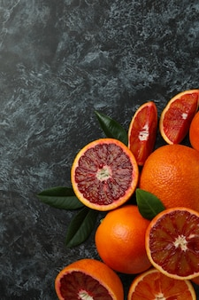 Red oranges and leaves on black smoky