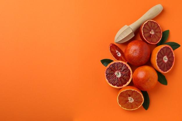 Red oranges, leaves and juicer on orange