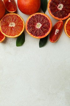 Red oranges and leaves on white textured isolated background