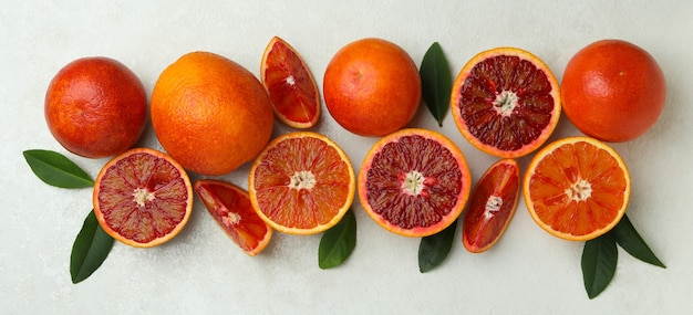 Red oranges and leaves on white textured