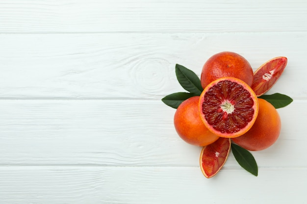 Red oranges and leaves on white wooden table