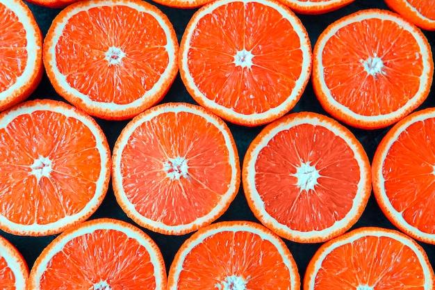 Красные апельсины или грейпфруты разрезают пополам на черном фоне.