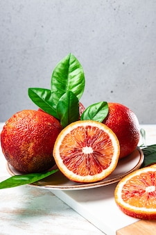 Красные апельсины целые и половинки на тарелке, вертикальное фото.
