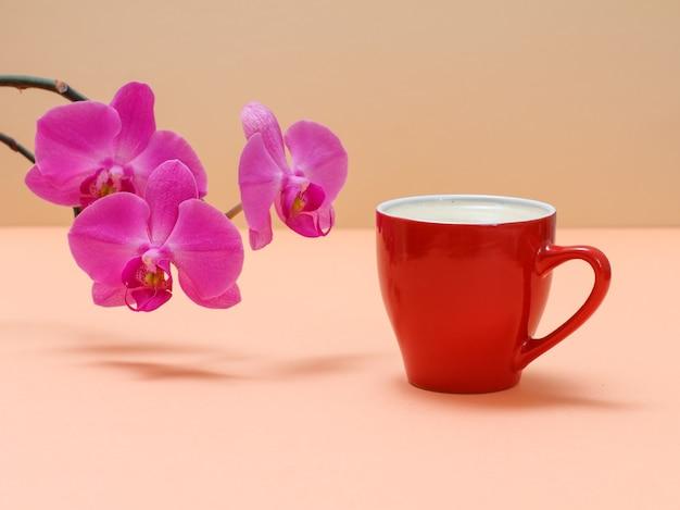 ベージュの背景にコーヒーのカップと赤い蘭の花。
