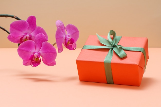 Red orchid flowers with gift box on a beige background.