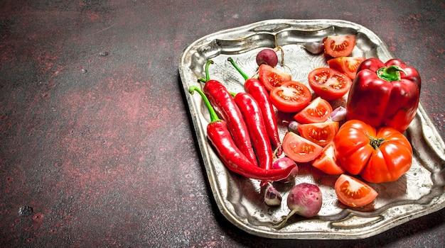 赤い有機食品。スチールトレイに新鮮な唐辛子、トマト、ピーマン。素朴な背景に。