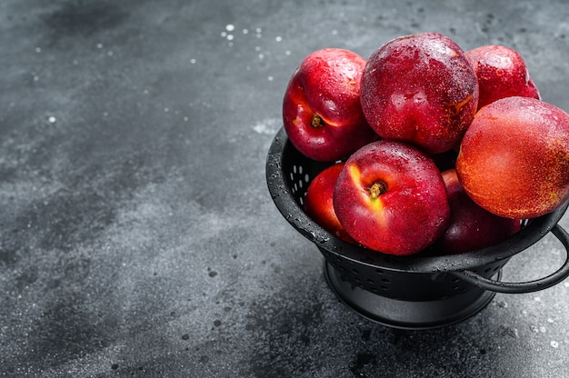 Red organic nectarines in a colander. black background. top view. copy space.