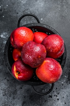 Red organic nectarines in a colander. black background. top view.