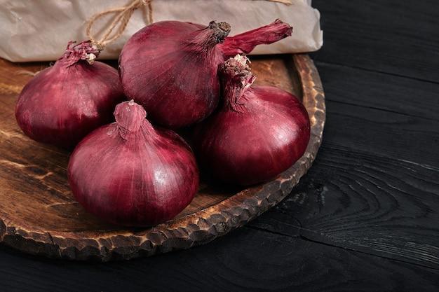 Красный органический лук пучок ферма эко овощи темный стол