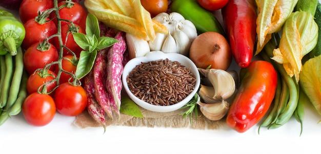 ボウルに赤の有機米と白で隔離される新鮮な野菜をクローズアップ