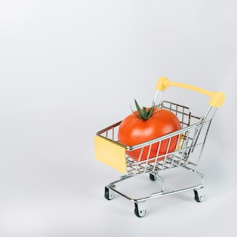 Red organic tomato in shopping cart on white background