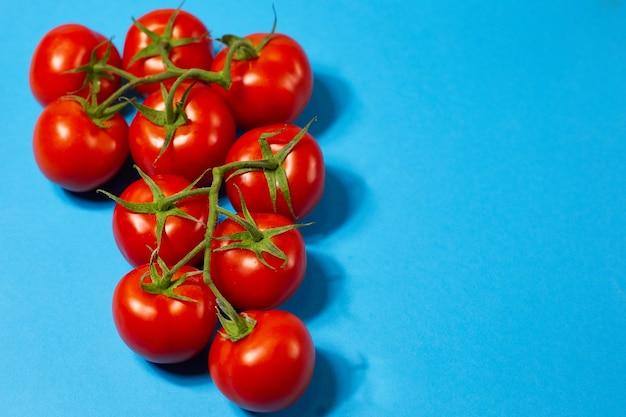青い背景の上の緑の枝に赤い有機トマト
