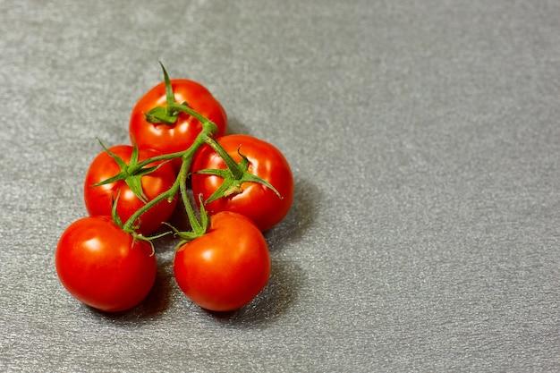灰色の背景の緑の枝に赤い有機トマト