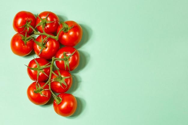 緑の背景の緑の枝に赤い有機トマト。