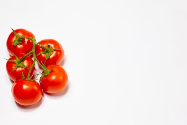 白い背景の上の緑の枝に赤い有機トマト。