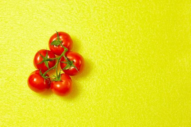 黄色の背景の緑の枝に赤い有機トマト