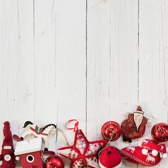 白い木製の背景の上のクリスマスツリーの赤い飾り