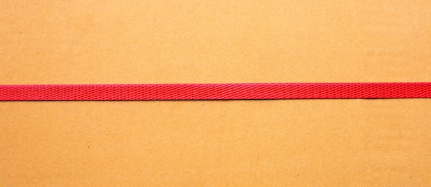 Red packaging straps on cardboard box