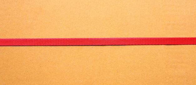 Красные упаковочные ремни на картонной коробке