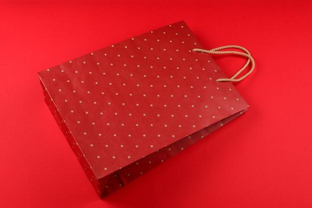 Красный пакет с точками в горошек на красном фоне. скопируйте пространство.