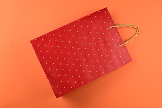 주황색 배경에 물방울 무늬가 있는 빨간색 패킷. 공간을 복사합니다.