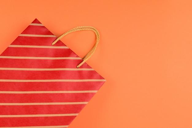 オレンジ色の背景の縞模様の赤いパケット。スペースをコピーします。