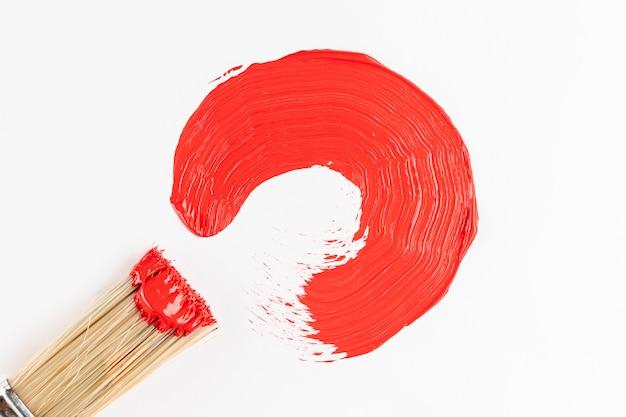 赤いペンキの半円とブラシ