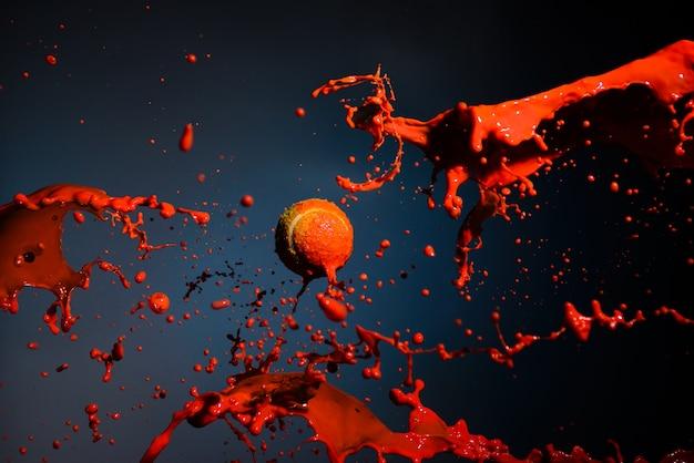 赤いペンキのスプラッシュとテニスボール