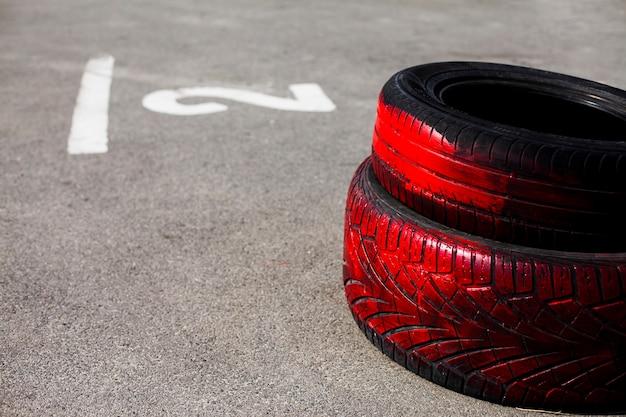 Покрашенные в красный цвет автомобильные шины на дороге
