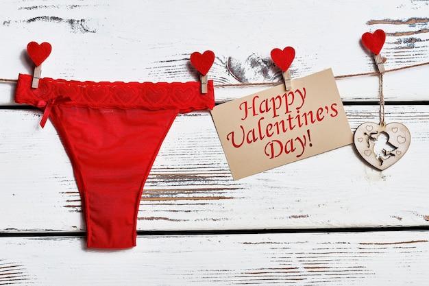 ロープの上の赤いパンティー。バレンタインカードとランジェリー。ガールフレンドへのセクシーな贈り物。