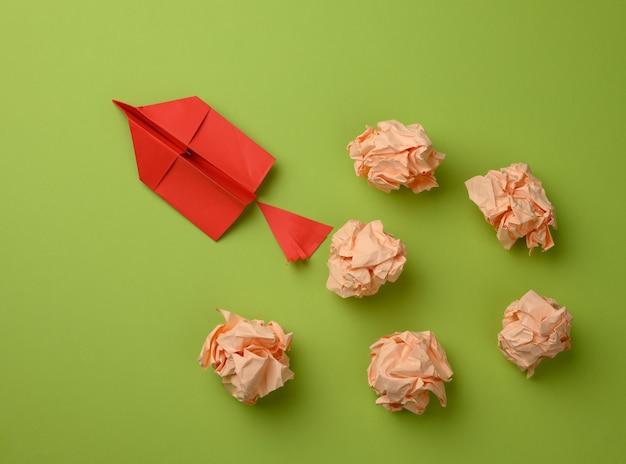 Красный бумажный самолетик и скомканные бумажные шарики на зеленой поверхности, вид сверху. концепция поиска новаторских идей, правильных решений. устранение ошибок и рывок вперед для лидера